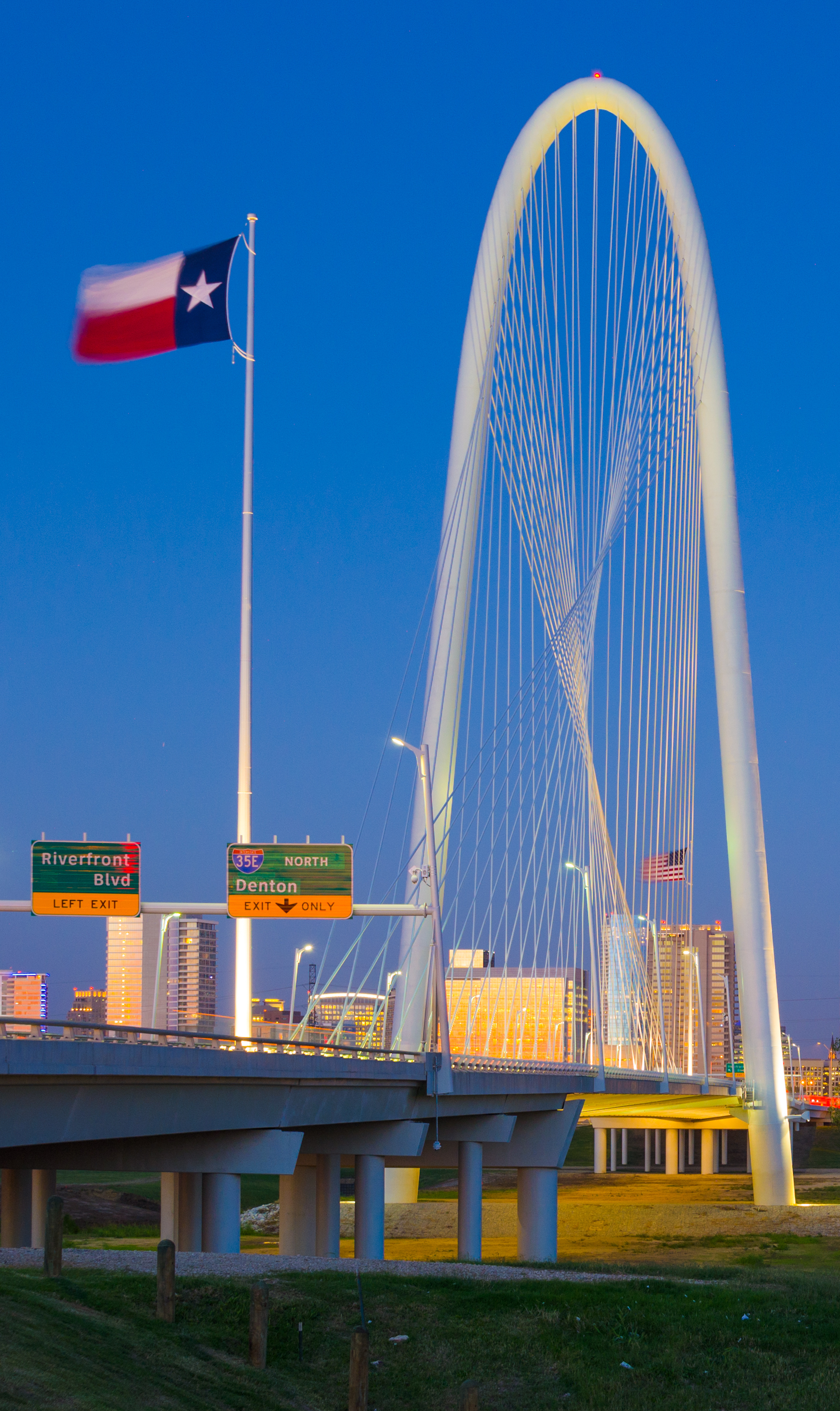 Dallas downtown skyline on the right with the Margaret Hunt Hill Bridge (going over the Trinity River) and the Texas flag on the left.